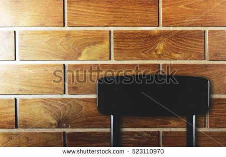 black chair with wood wall background over light and dark tone