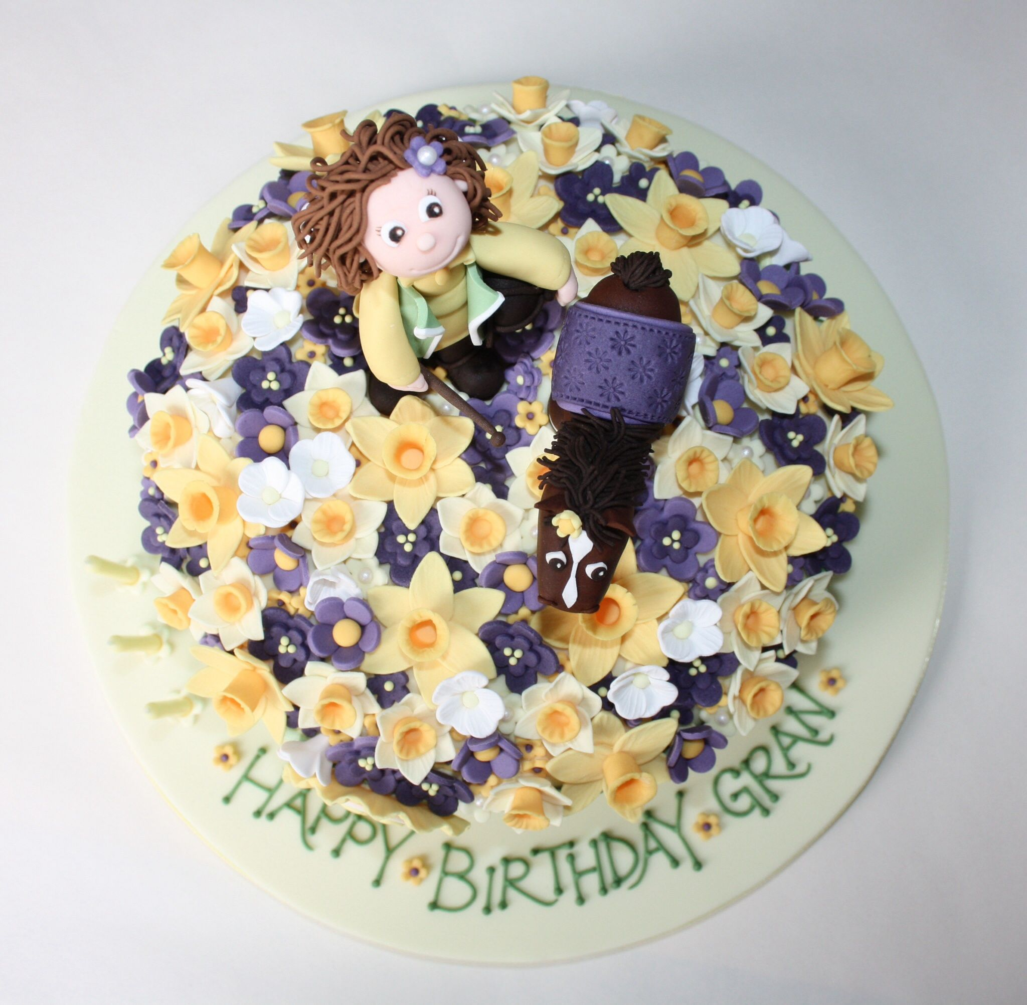 Top view of the 60th birthday cake I made for my friend's mum. A little horse and rider standing in a field of purple and yellow spring flowers with a few daffodills.