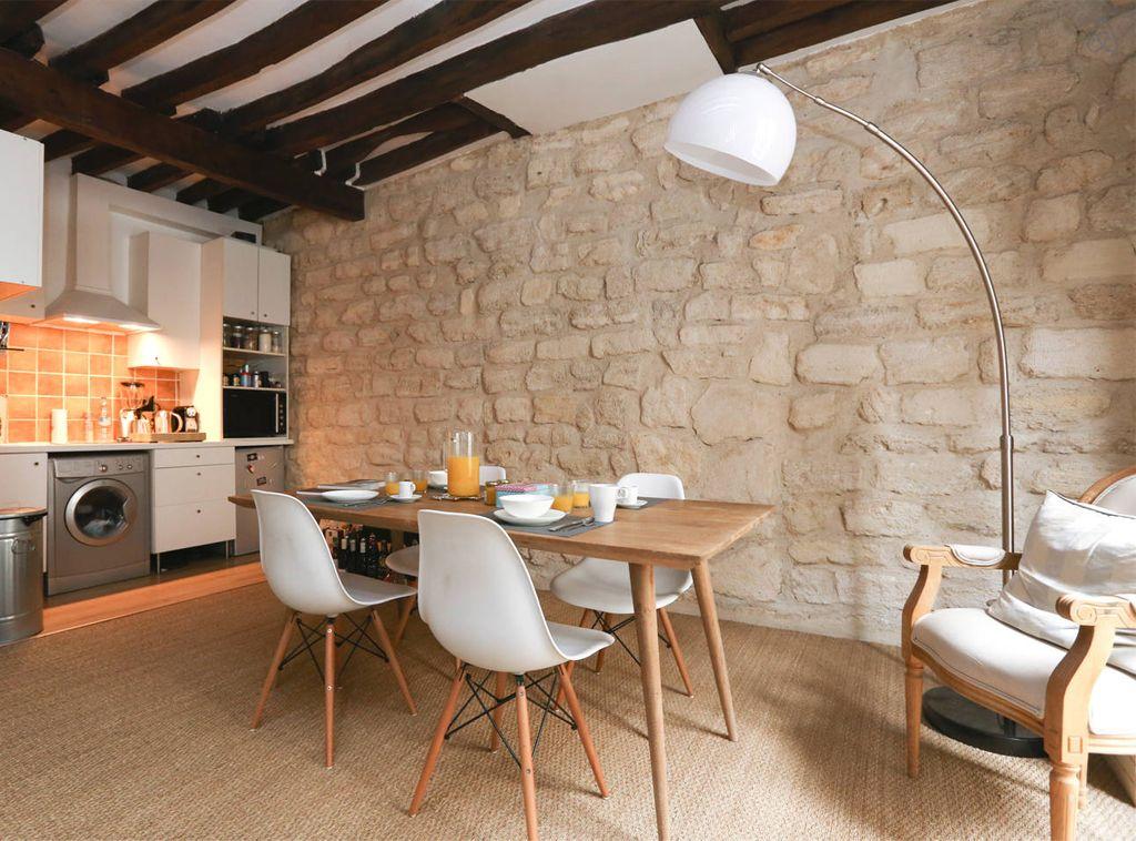 d coration d 39 un salon avec chaises eames table bois scandinave poutres et pierres apparentes. Black Bedroom Furniture Sets. Home Design Ideas