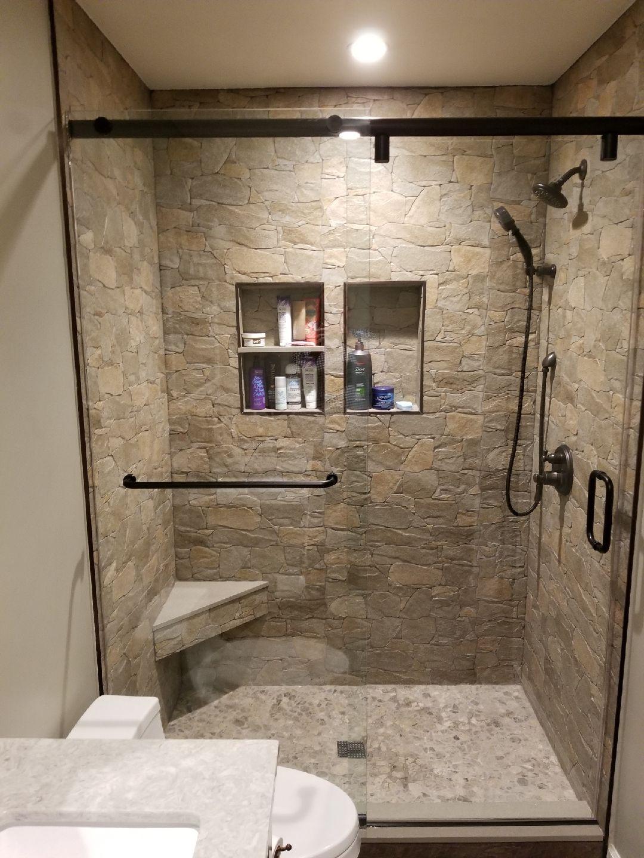 Shower with rock ceramic tile, river rock floor, quartz