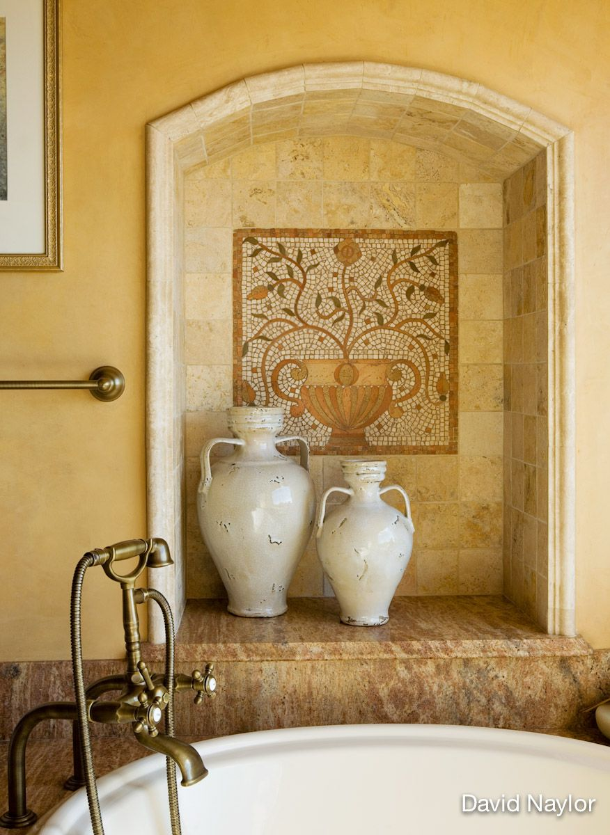 This nicho's interest is deepened with a flowering Italian mosaic inset surrounded by stately travertine tile and molding. Two eggshell-glazed vessels sit atop the Algerian marble, which has the pleasantly variegated striations of a marled-wool sweater.