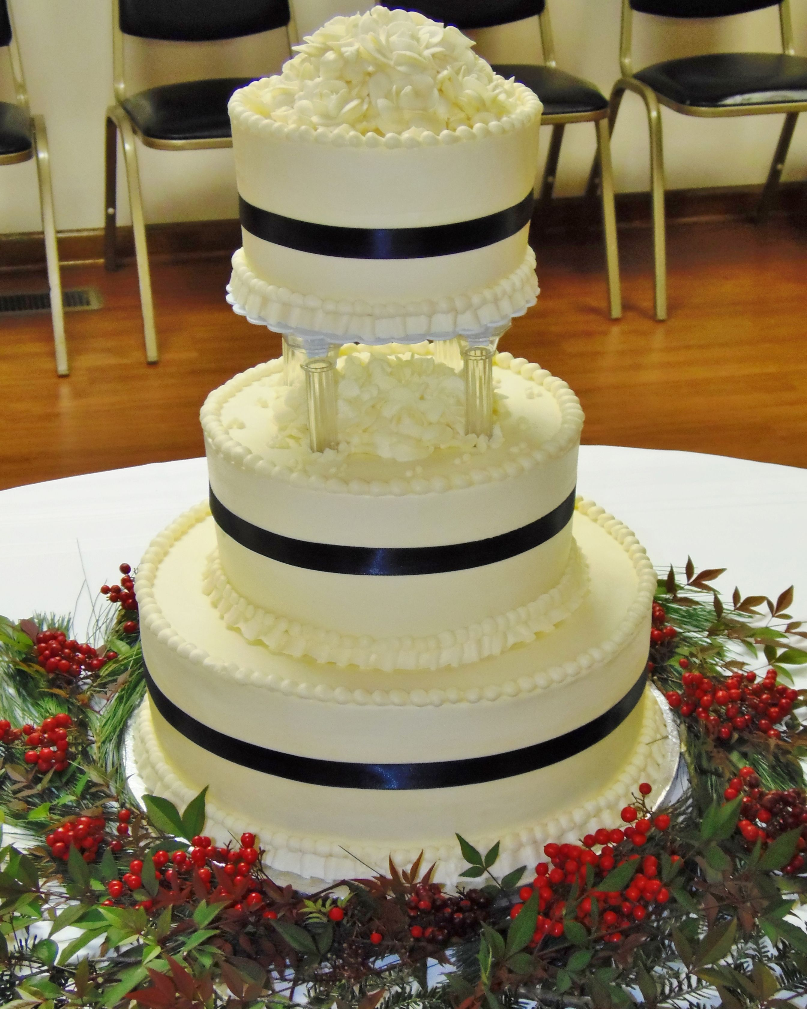 3-tiered wedding cake with top tier elevated on clear columns. White ...