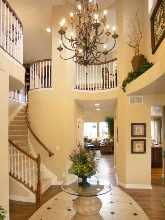Elegant chandelier an elegant chandelier makes a grand statement in this double height entryway recessed fixtures provide additional ambient lighting