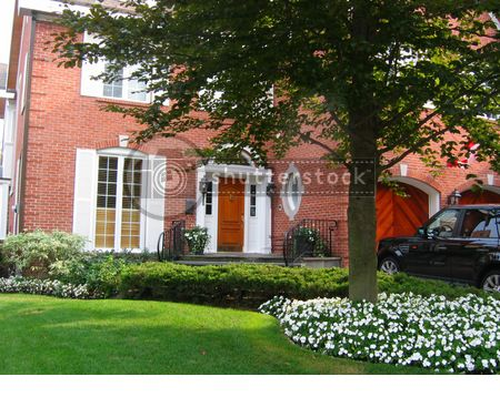 Red Brick House With White Shutters And Bright Green Manicured