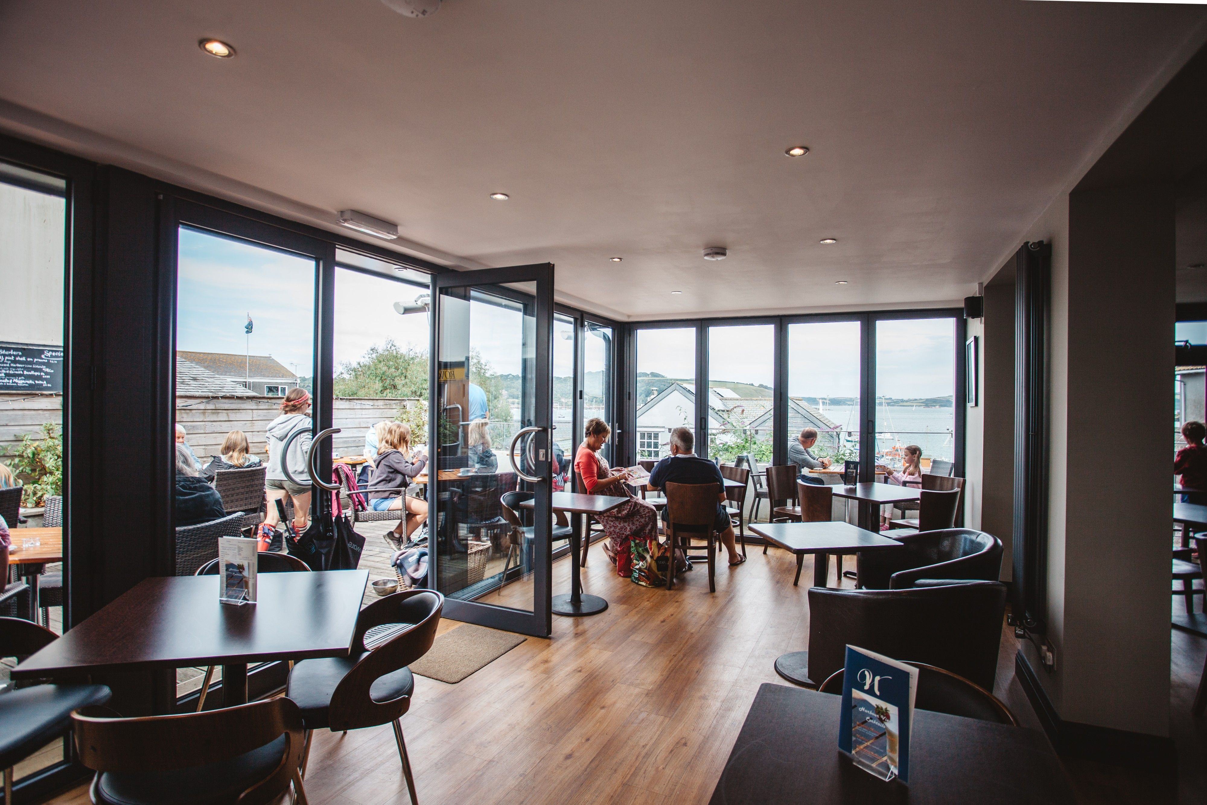 open interior which merges with the outdoor seating by the use of large glass windows and bi fold doors to give the cafe a welcoming feel - Large Cafe Interior