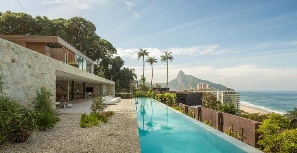 Immersa nel verdissimo paesaggio carioca, tra montagne e Oceano, una casa in legno e pietra con piscina panoramica