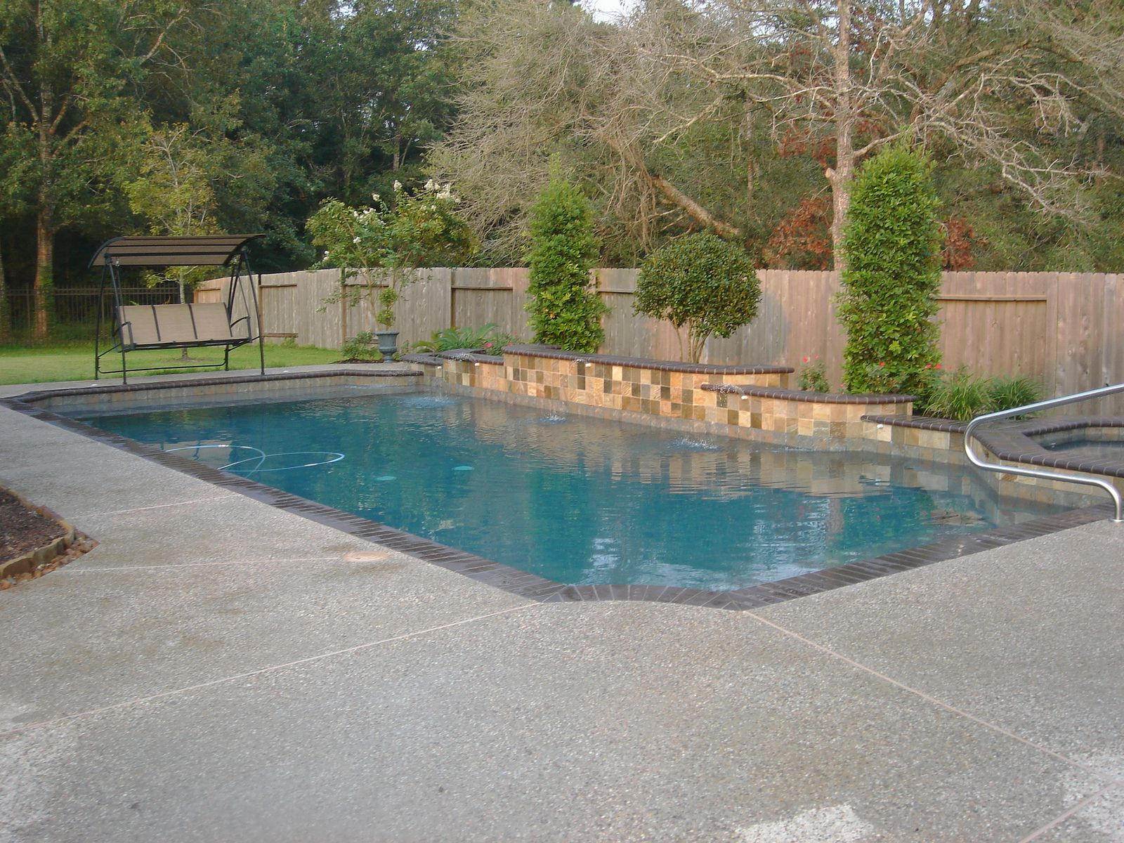 Design Simple Swimming Pool With Fountains And A Swing Seat