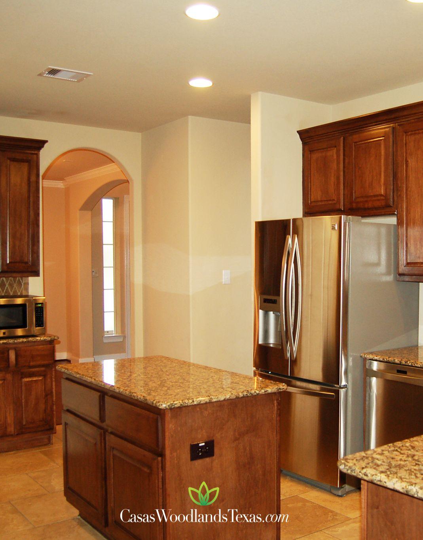 La cocina cuenta con encimeras de granito y gabinetes de madera ...