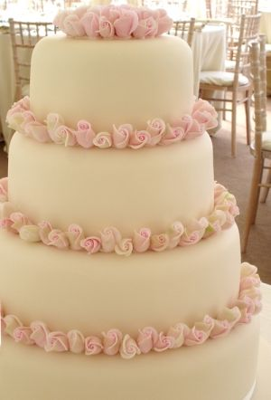 Four tier cake packed with sugar sweet avalance rosebuds. Cake by Nicky Grant. www.nickygrant.com