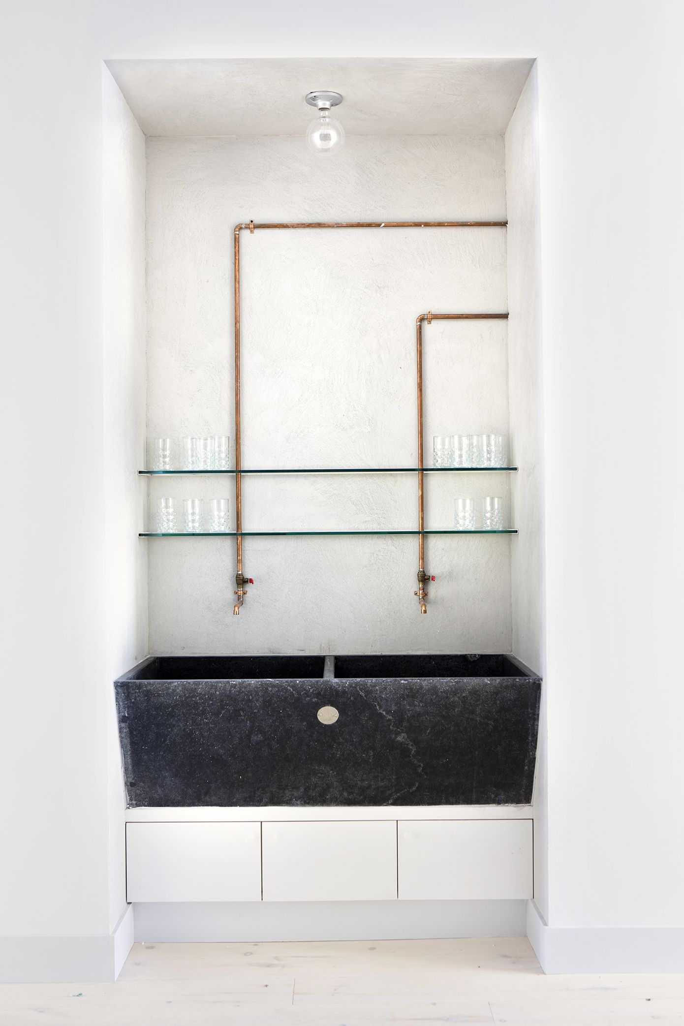 Raw stone sink in a modern setting with exposed copper - Commercial kitchen plumbing design ...