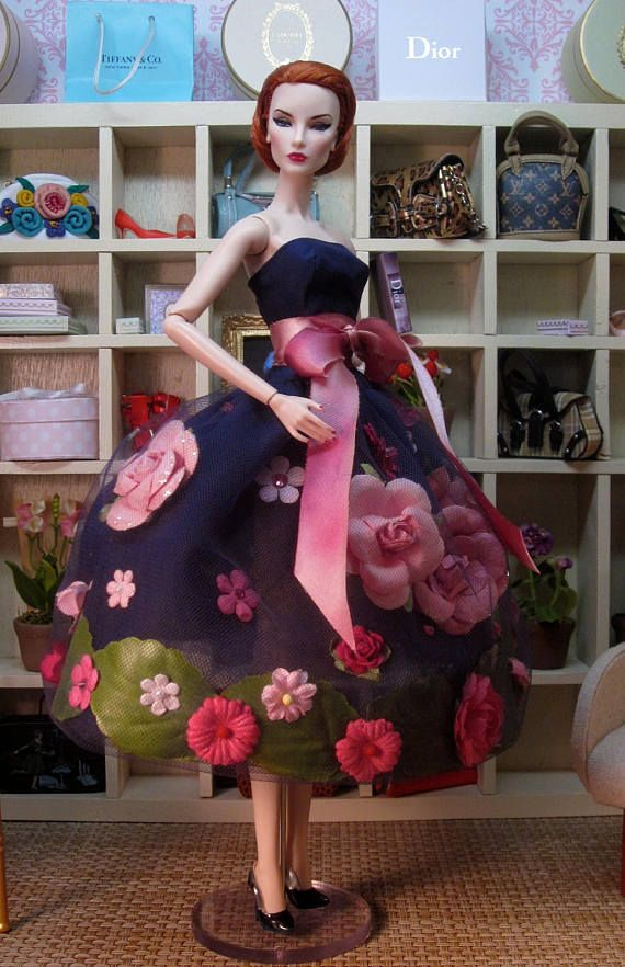 The tenth gown in a series honoring my mother Nancy and her love of flowers. The gown is a classic combination of navy blue tulle with pink roses. The strapless bodice has a peplum silhouette and is made from navy blue silk taffeta. The voluminous skirt is made from 8 layers of soft vintage navy tulle. Encased in the tulle are roses in various shades of pink, with a line of glossy green leaves along the bottom. A sprinkling of pink Swarovski crystals adds sparkle. This fashion fits…