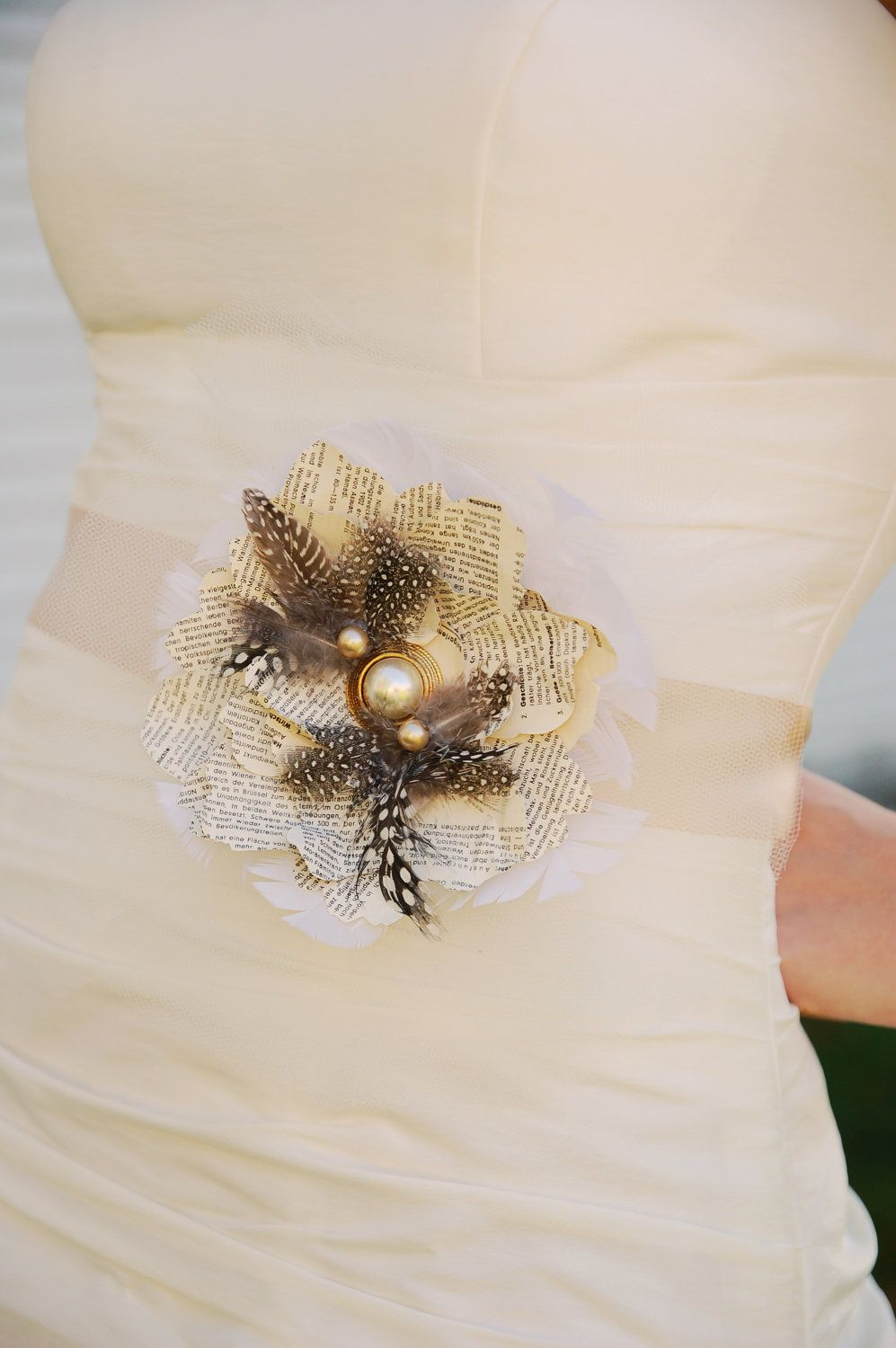 Be Elegant. Black and white flower wedding sash, with a vintage Book paper flower with pearls and feathers. $148.00, via Etsy.