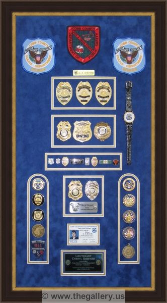 Cobb County Police Department retirement shadow box with police badges, patches, ID cards and lapel pins.