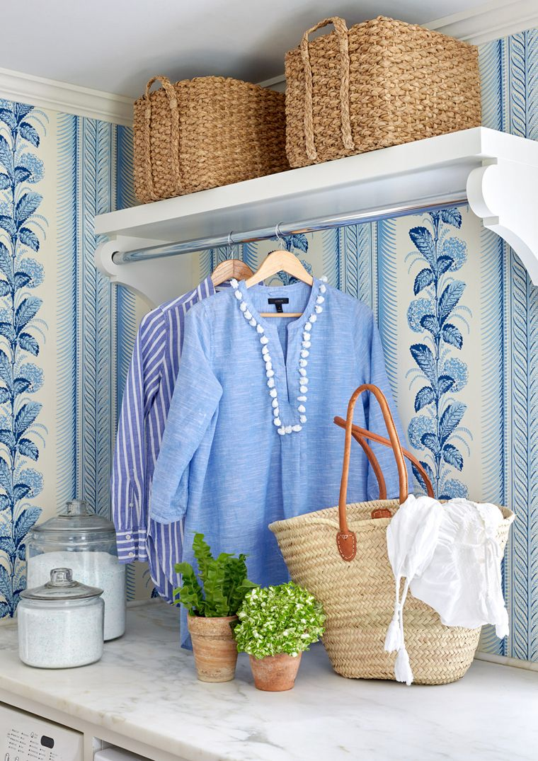 Blue laundry room by Sarah Bartholomew. Because Bartholomew spends so much time in the laundry room, it was important to her that it be pretty. She papered the walls with Quadrille's Climbing Hydrangea and keeps the space filled with plants.