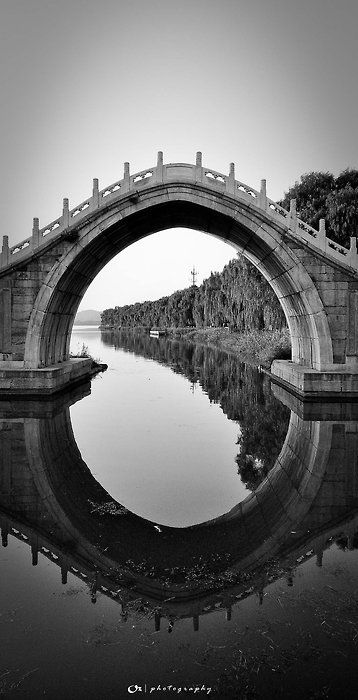 The reflection and shape of the bridge is incredible and the way it frames the tree line is really cool photographer unknown