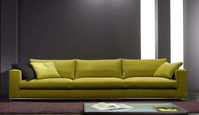 Divano verde senape abbinato al colore grigio della parete for Il colore nell arredamento