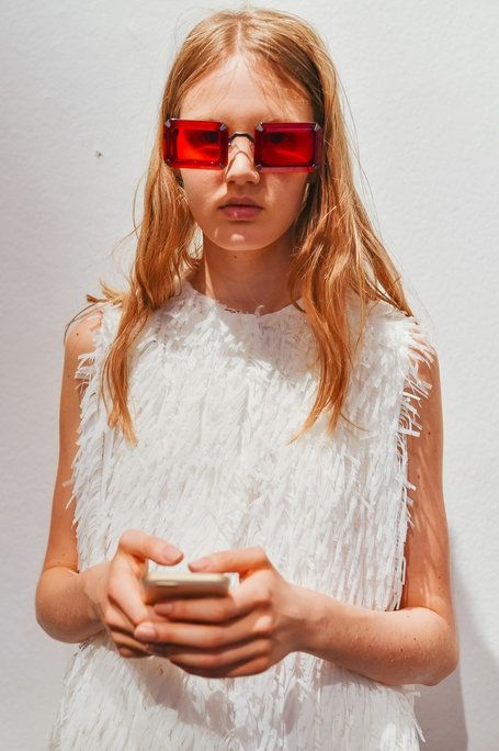 Backstage at Marco De Vincenzo, a model took a break to look at her phone — through rose-colored glasses. (Photo: Piotr Niepsuj)