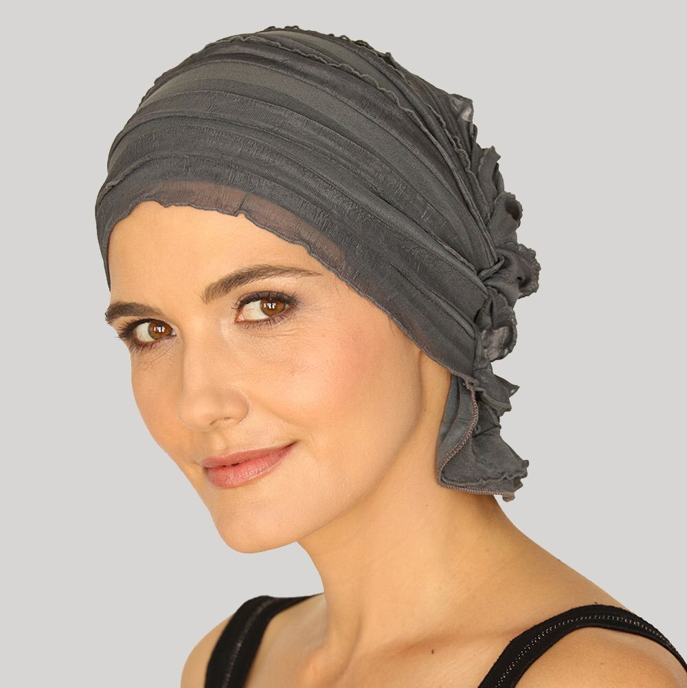 Our patented design was created for comfort and ease of use. No tying or mirror required. Just slip on and go!  Each Chemo Beanie bares the name of a woman who has taken the journey. Our original ruffle design gives more volume and the flap on the back of the neck provides full coverage of the bald head.  Charcoal Grey Ruffle.  Machine wash cold/lay flat to dry 93% Polyester 7% Spandex - $24.99