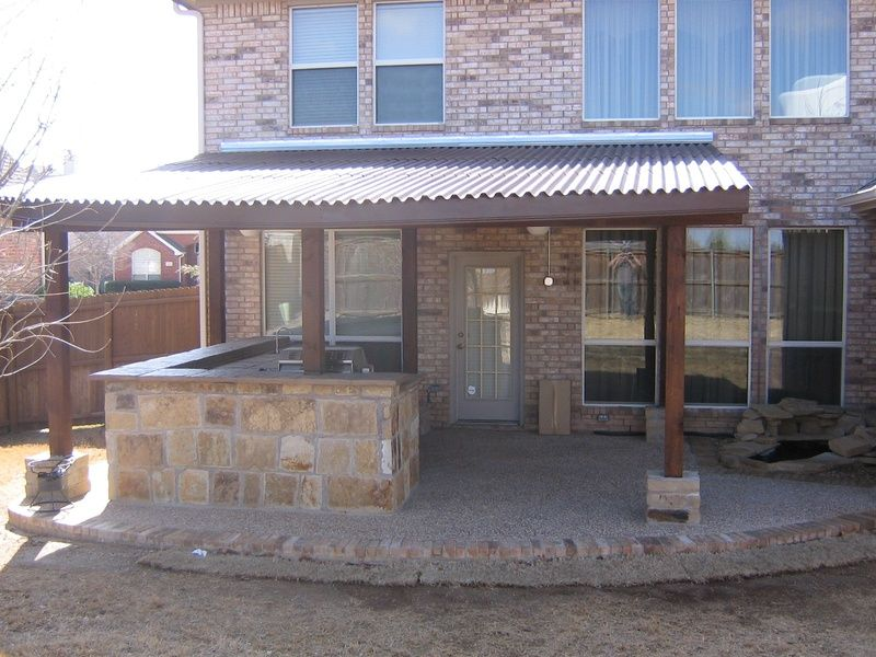 Nice Patio Cover With Synthetic Roof And Stone Pillar Accents