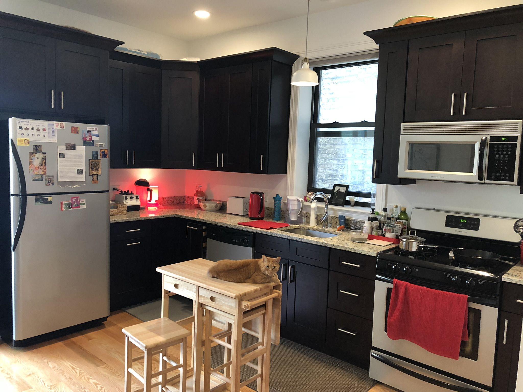 Modern kitchen with black cabinets pendant lighting hardwood