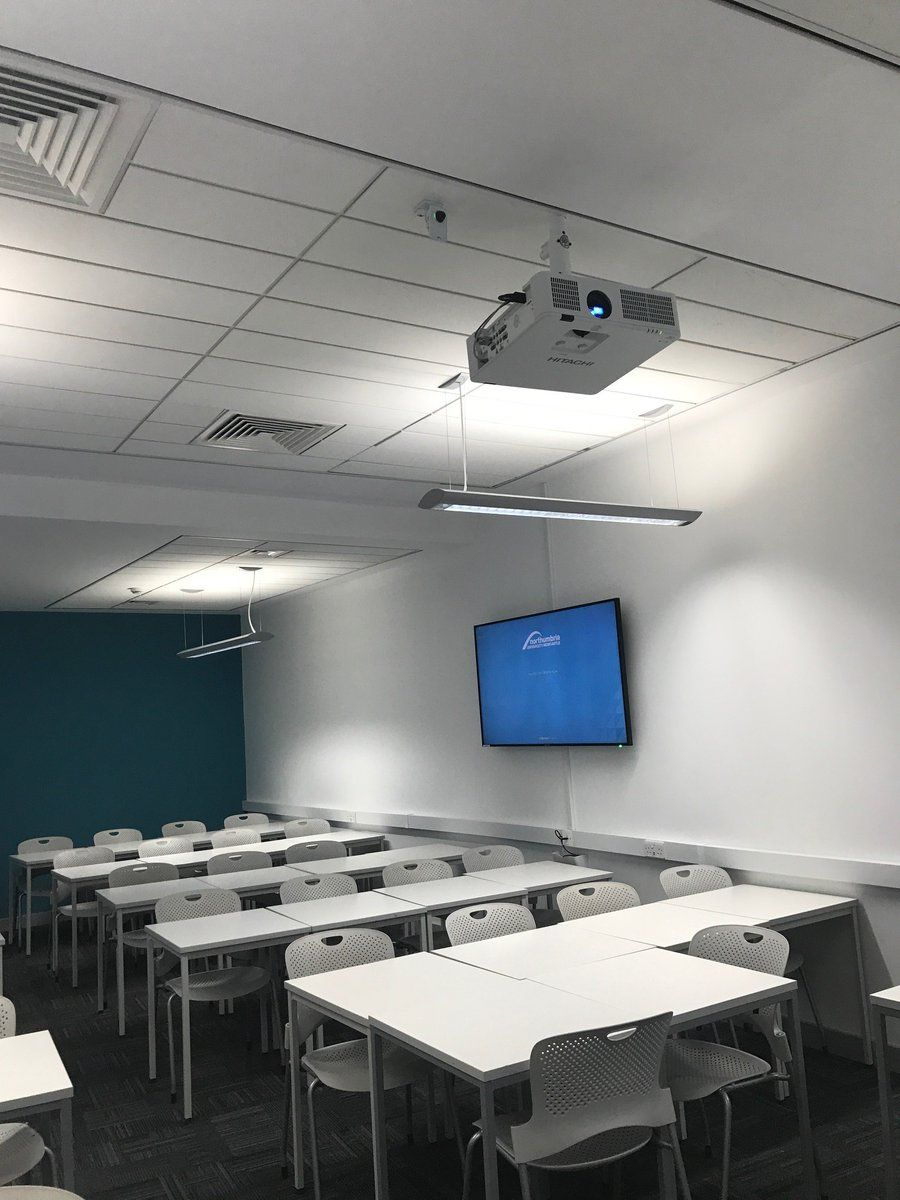 A Hitachi Projector Mounted To The Ceiling In A Classroom