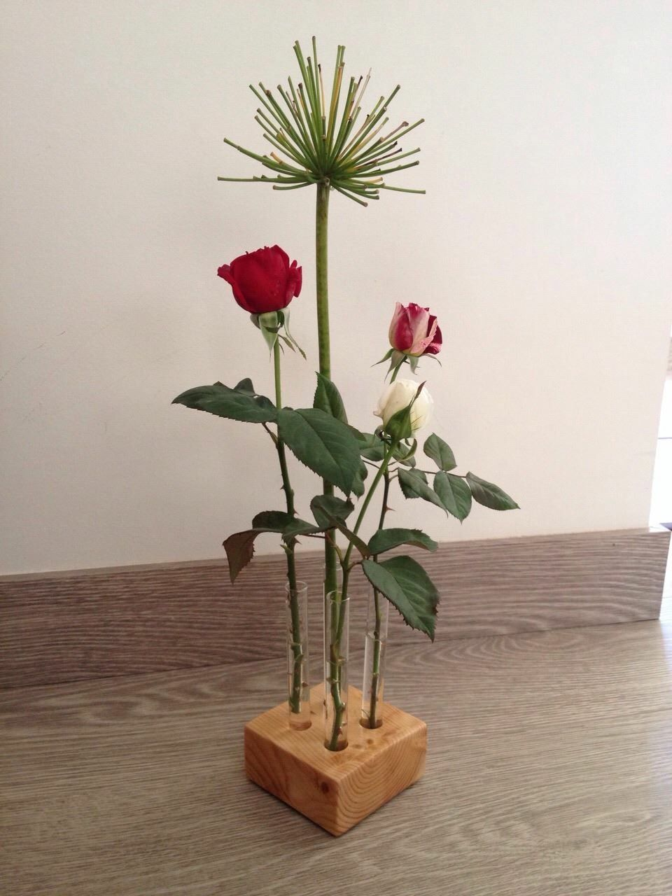 Bonito florero hecho con tubos de ensayos de cristal y su base hecha con parte de un palet de madera reciclado.