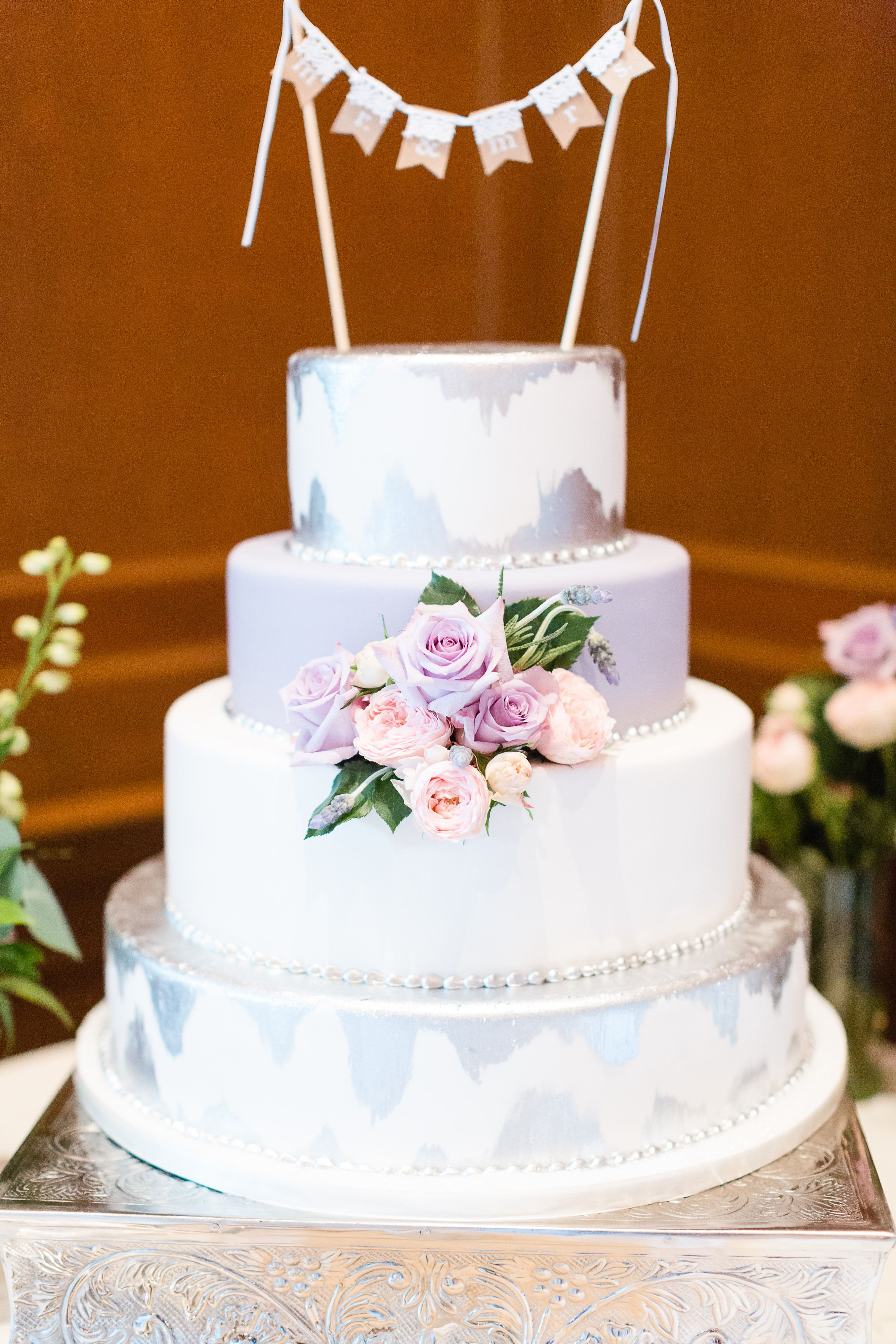 Gorgeous four tier cake with purple & light pink roses in the center ...