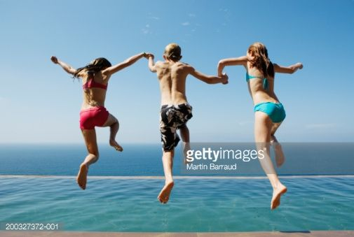 Two Girls And Boy Holding Hands Jumping Into Pool Rear View