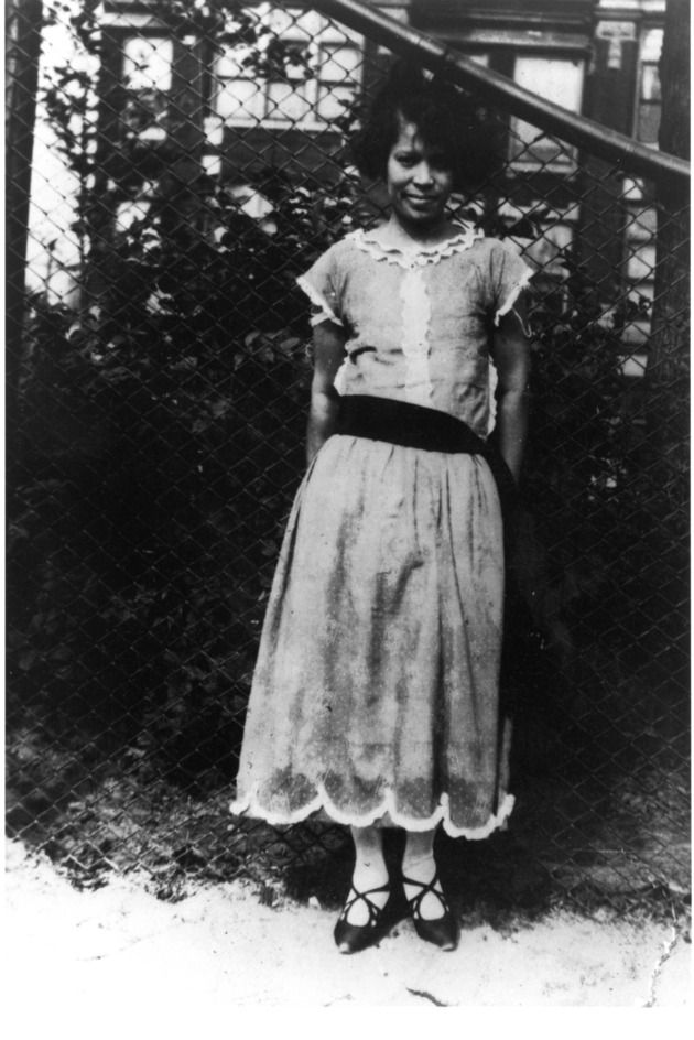 Zora Neale Hurston Outdoors Leaning Against A Chain Linked