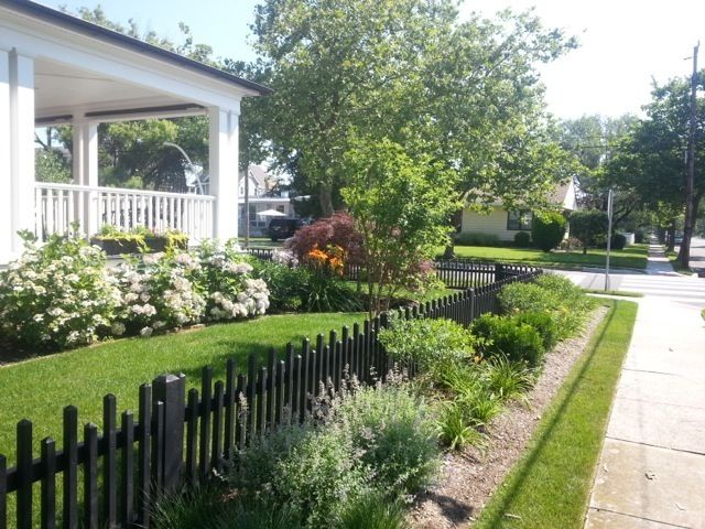 Black picket fence and perennial plantings at property for Beach house yard ideas