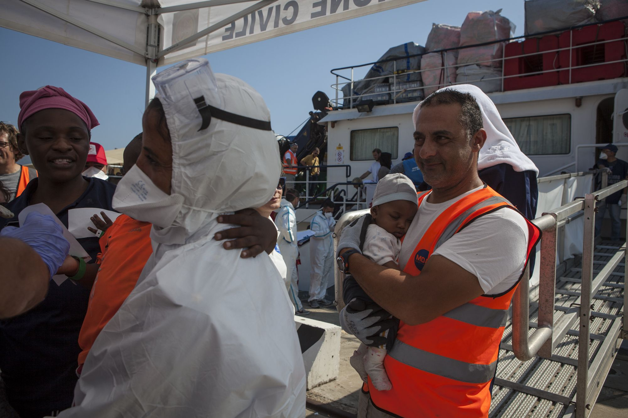 Mimmo one of the members of the MOAS search and rescue team who had help save 4 month old Daryl and his family two days before, carries him ashore at the port of Messina, Sicily. image © Jason Florio/MOAS_EU, 2015. All rights reserved