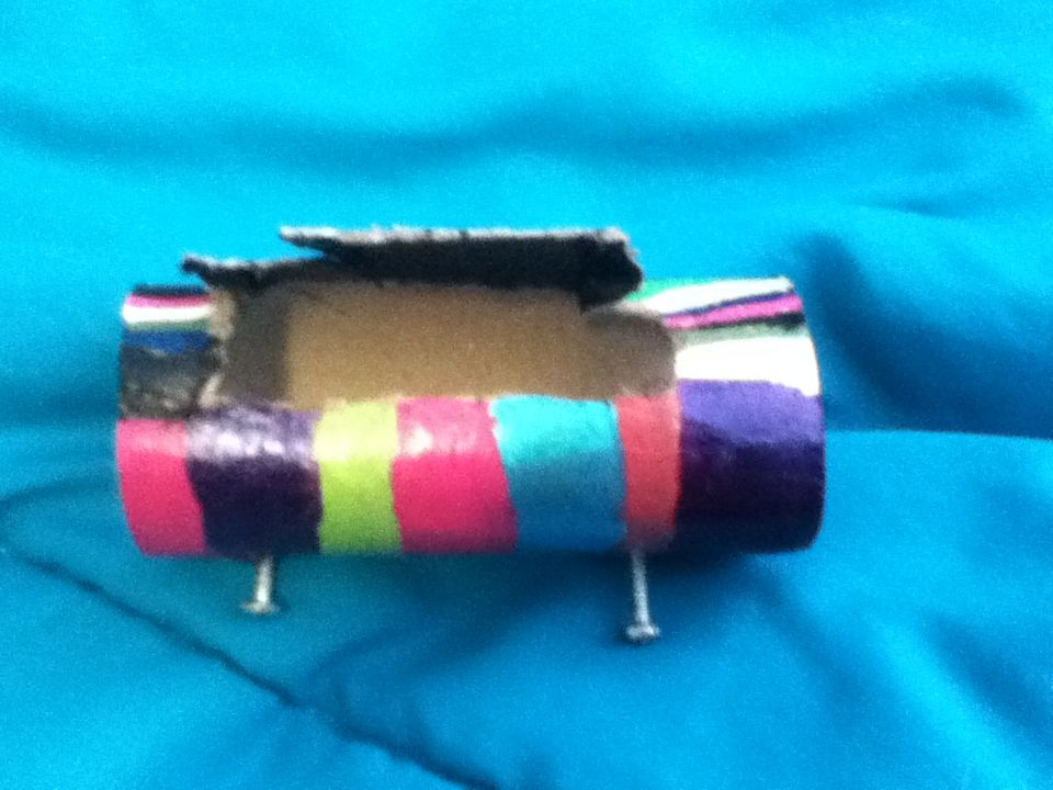 My homemade iHome. My lil bro got the idea from his art teacher u take a toilet paper roll with no toilet paper on it, put 4 holes it the bottom corners then place screws that fit then u can if u want cut a rectangle in the bottom for ur charger it works when I play music it is loud I painted it when I was bored with nail polish 2 haha