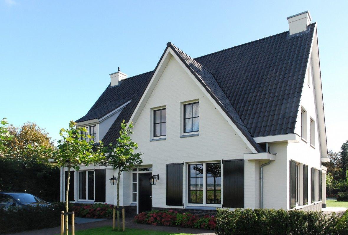 De witte gevel in combinatie met de donkere accenten geeft villa