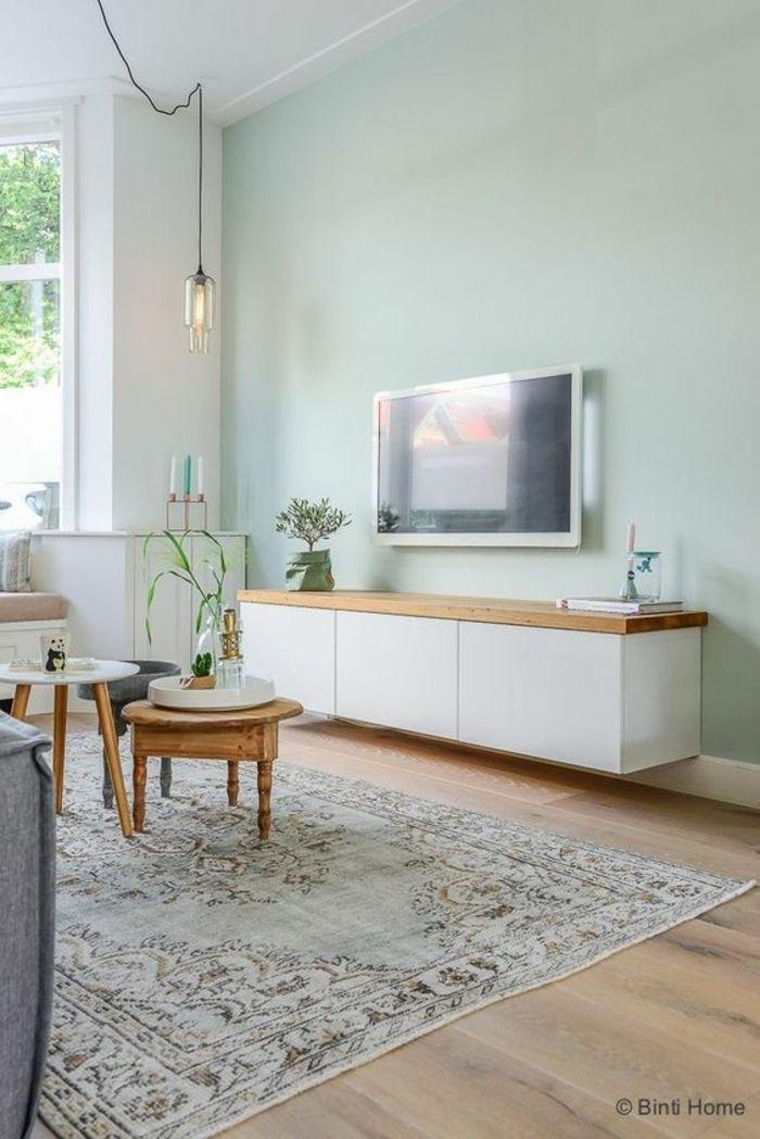 Photo of To-tone stuevegger, lys grønnblå vegg, motsatt hvit vegg med … – trebord …