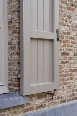 Putty colored shutters with overgrouted brick.: