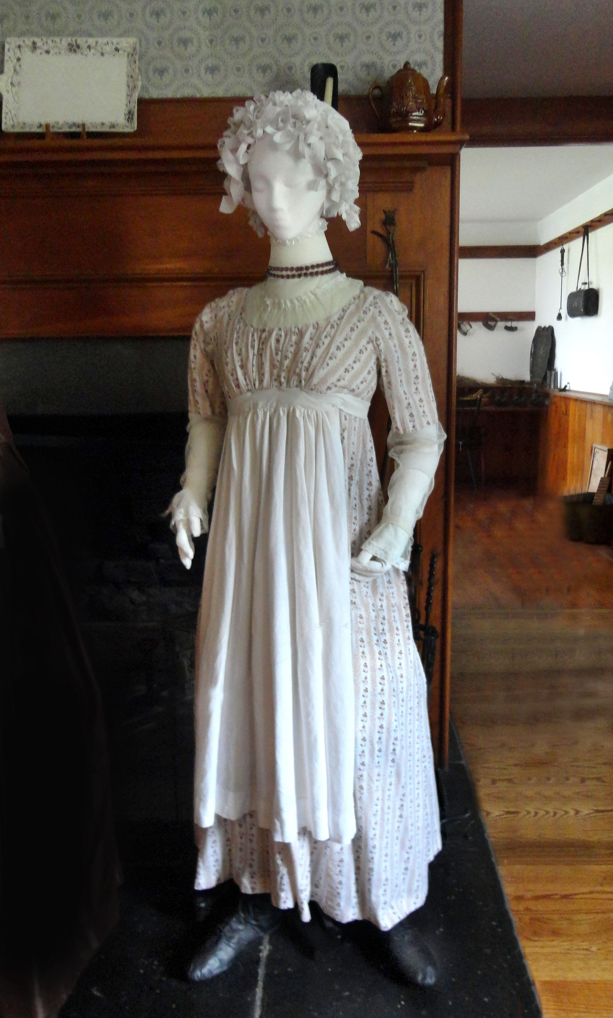 Housemaid, Vine Print Day Dress, 1790s Dress based on pattern in The Cut of Women's Clothes, by Norah Waugh. White and pale pastels are colors associated with Neo-classical styles, but one-piece dresses like this one show that delicate prints were also popular. The 'round gown' had the bodice and skirt sewn to form a one-piece dress. The outfit is accessorized with a lace cap and linen apron.
