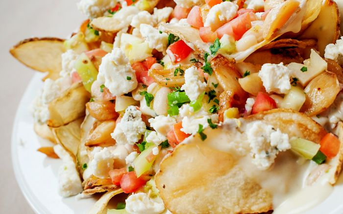 Bayou Chips - Homemade kettle chips smothered in our bleu cheese sauce, white bean relish, roasted garlic topped with bleu cheese crumbles add grilled chicken, ground andouille or ground hot sausage ...