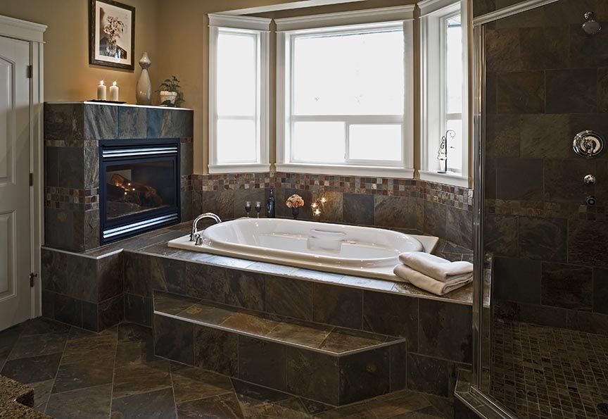This custom ensuite was built in Langley featuring natural slate bathroom, body sprays, jacuzzi tub and two sided fireplace.
