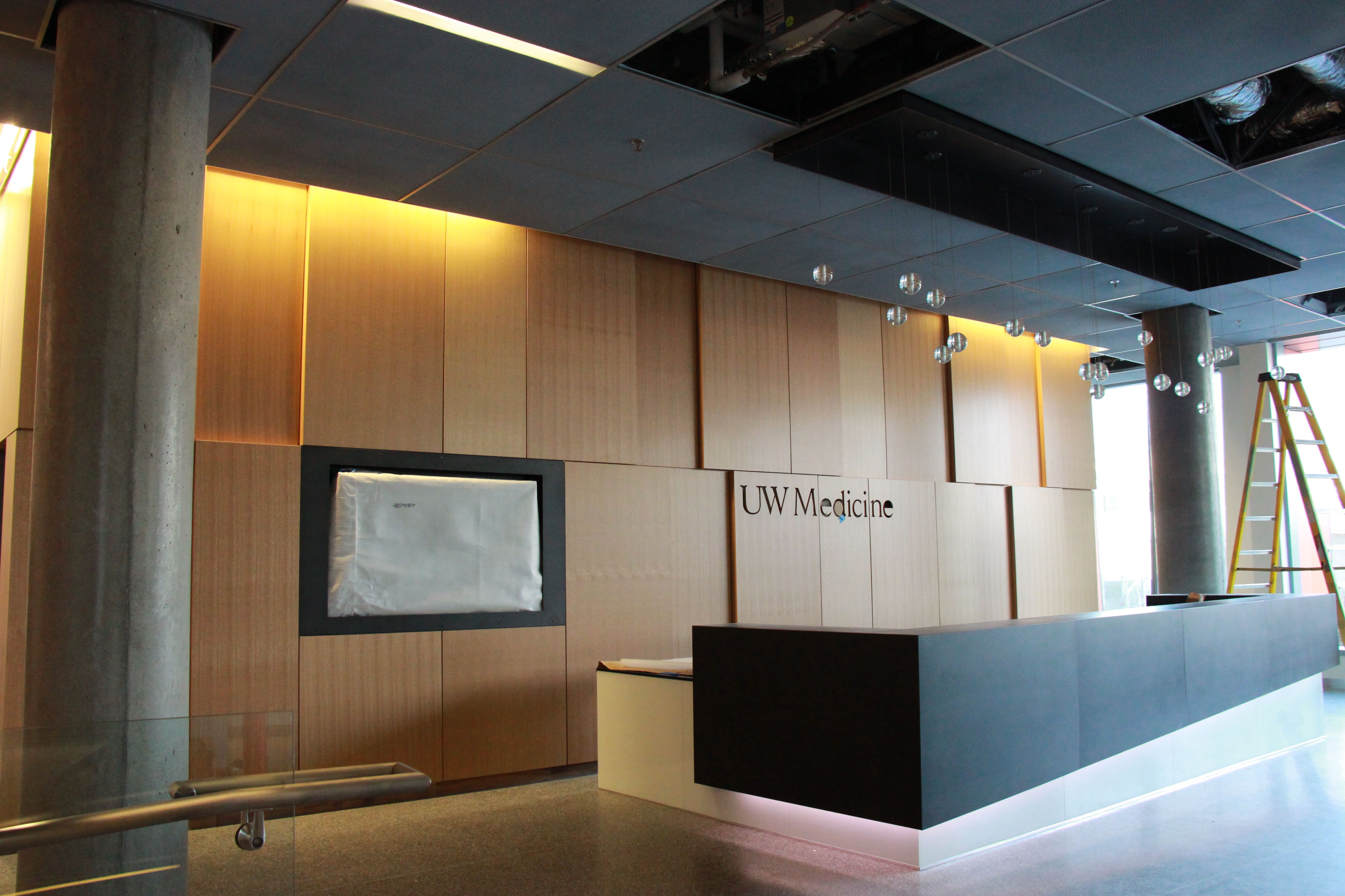 Laser logo on wall behind reception panels hide storage for Reception area design ideas
