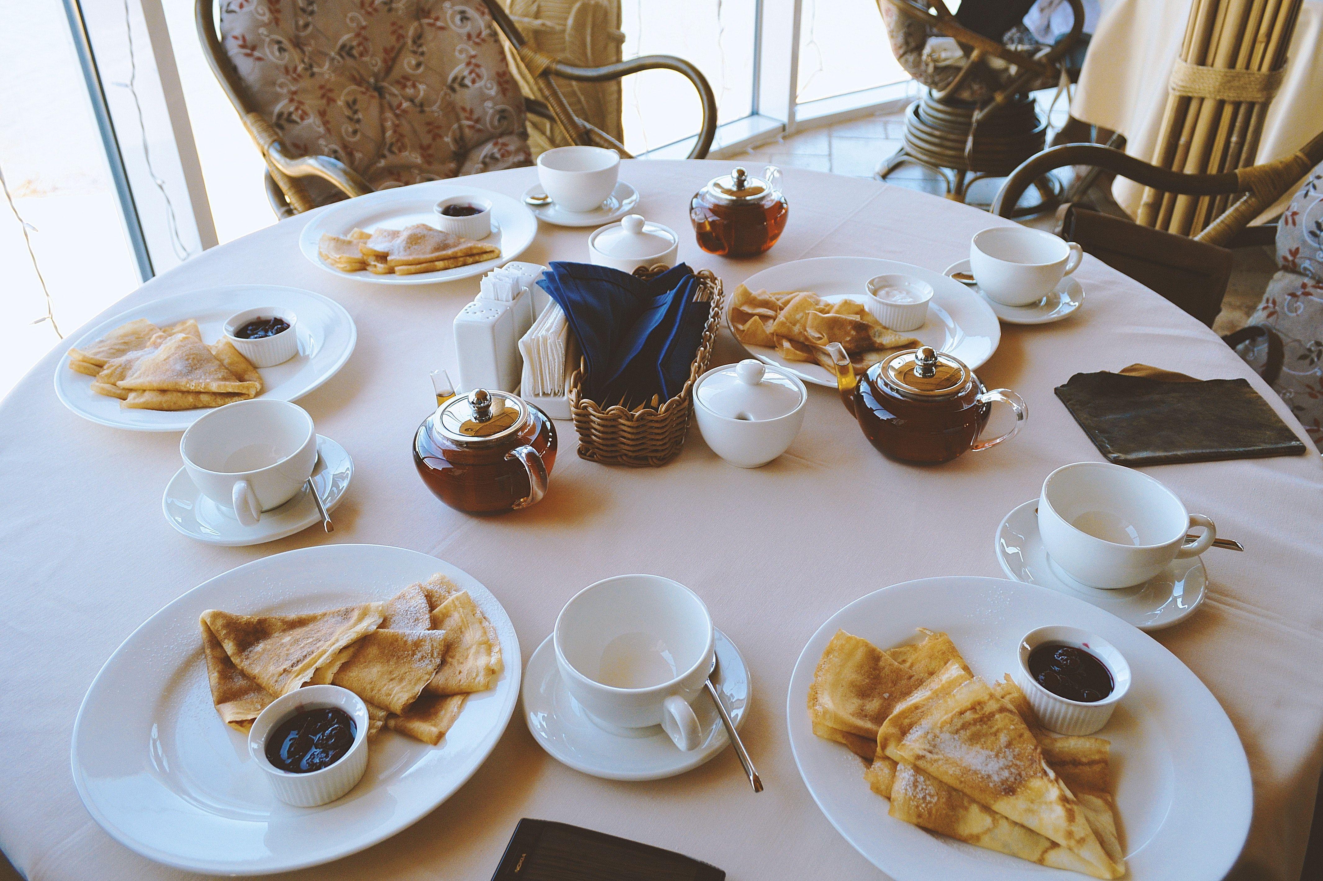 White Ceramic Dinnerware on Table, breakfast chairs