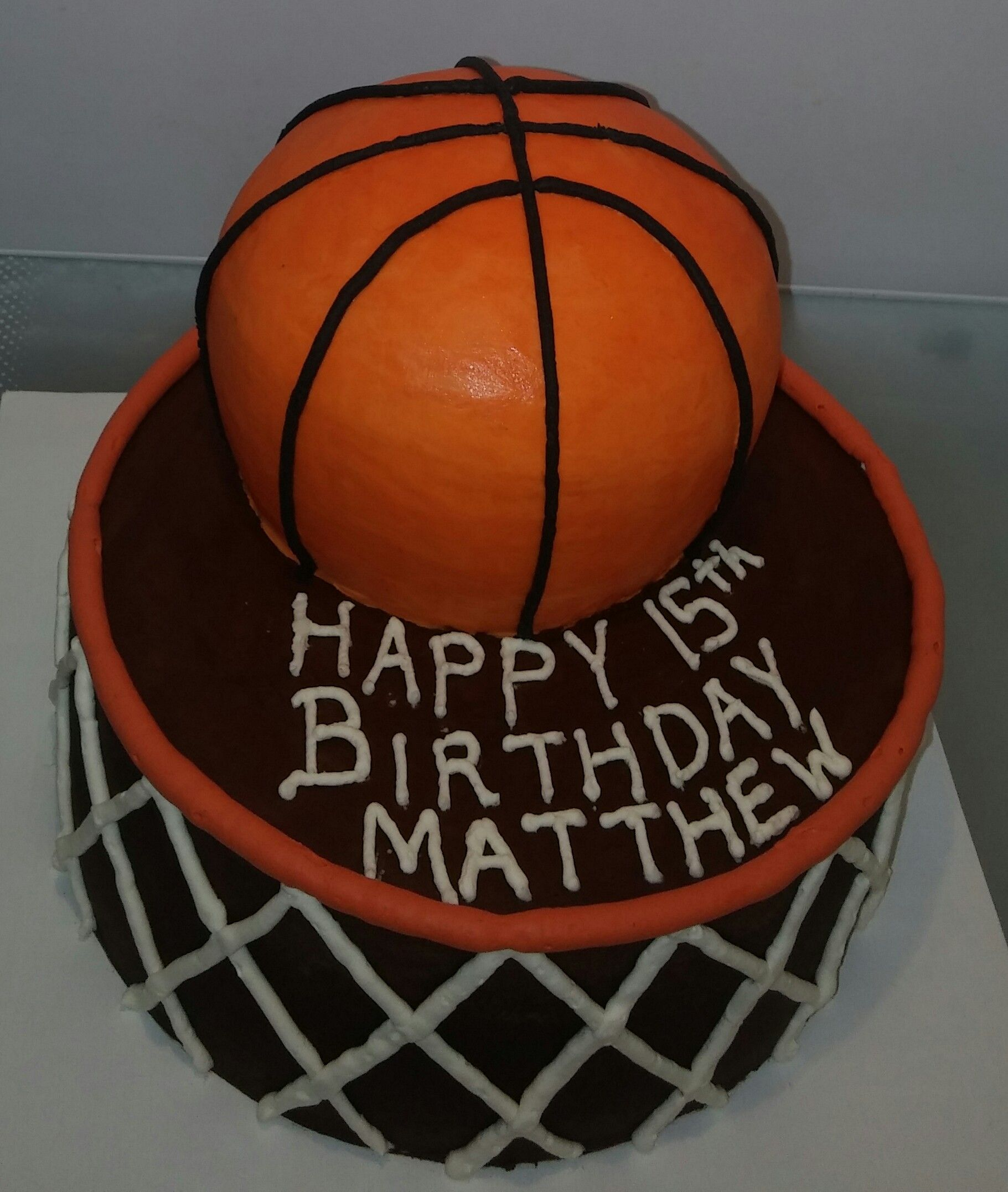 This was a  basketball themed cake made of chocolate cake and chocolate frosting. Basketball was all cake with a chocolate frosting and buttercream frosting on top. No fondant was used.