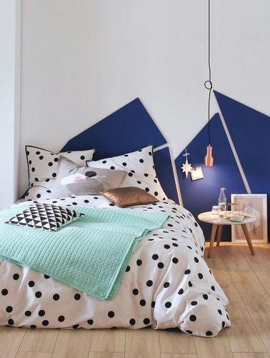 une tete de lit geometrique avec du linge de lit a pois