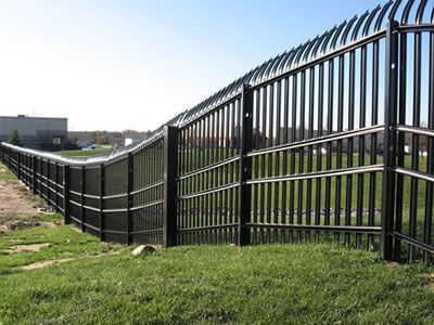 On A Vast Grassland A Row Of High Palisade Fence Follow The Uneven Terrains Security Fence Backyard Fences Dog Fence