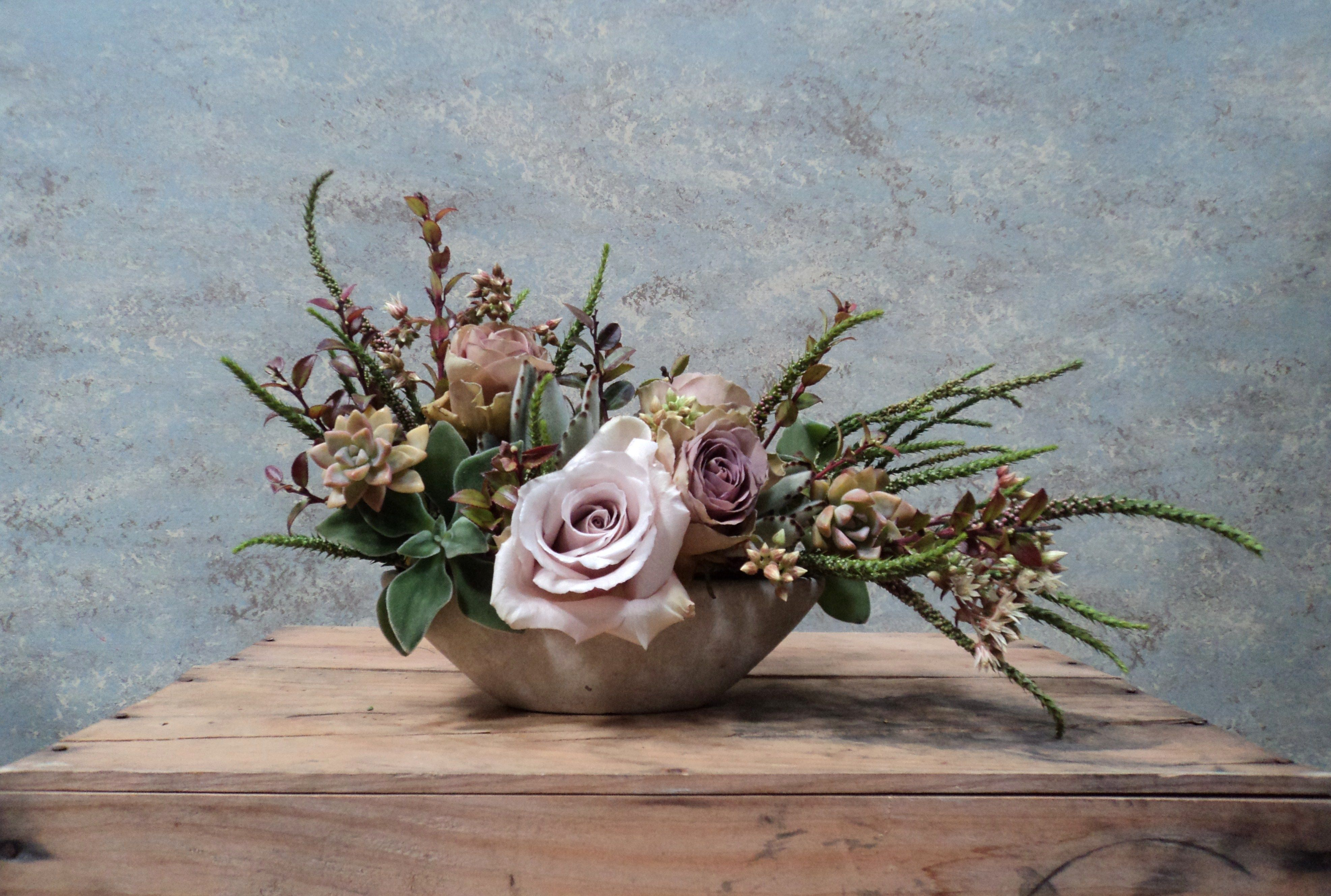 Dandelion Ranch... Lavender roses with minty foliage and purple tinged bronze succulents.