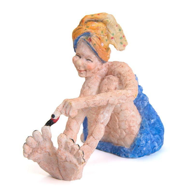 Sjov figur med pigen, der gør sig klar til en tur i byen. Hun sidder indpakket i et blåt håndklæde og med endnu et spraglet håndklæde viklet om håret. Hun sidder og lakerer sine tånegle, så hun kan set godt ud til en tur ud i nattelivet. Størrelse på figur: Længde 15 cm. Bredde 10 cm. Højde 13 cm.