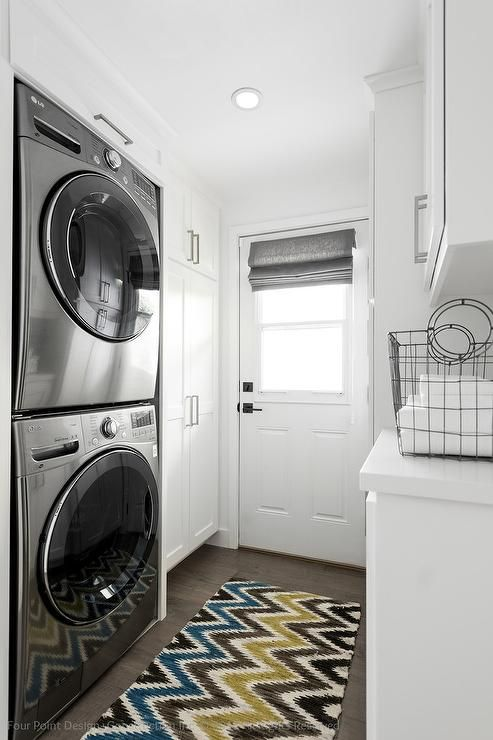 Charmant Small White Laundry Room Features Floor To Ceiling Cabinets Placed Next To  A Stacked Washer And Dryer Tucked Into The Wall Alongside A Blue, Yellow,  ...
