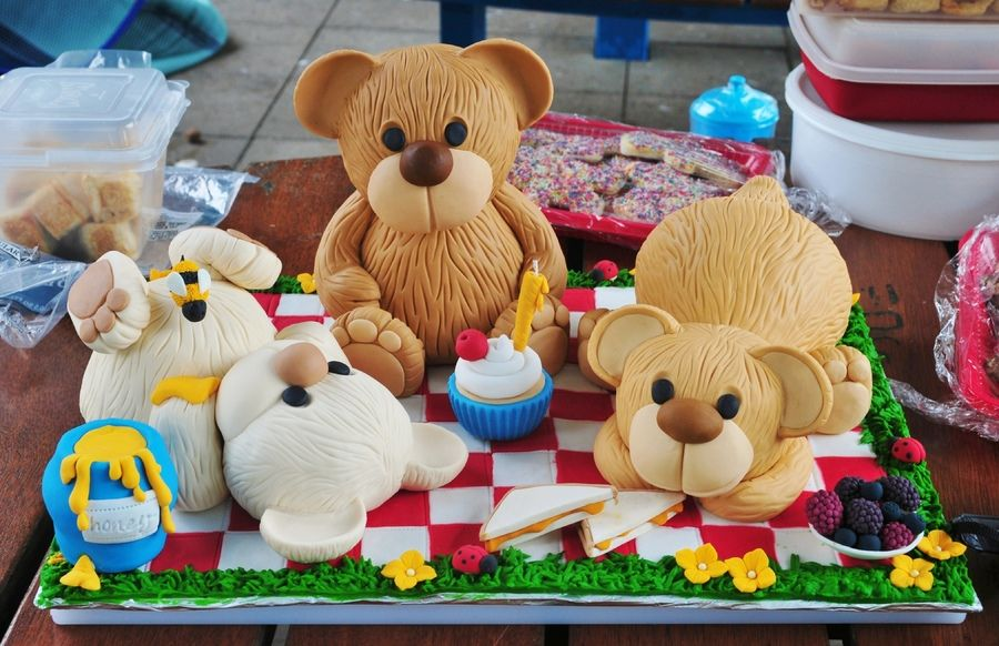 Teddy bodies made using dolly varden tin with white choc fudge cake. Heads made with rice crispies and all covered with fondant. Ears, faces, arms, legs and teddy bear 'snacks' are all modelled from gum paste. Royal icing grass and fondant picnic, making it 100% edible and completely devoured for my son's first birthday. :)