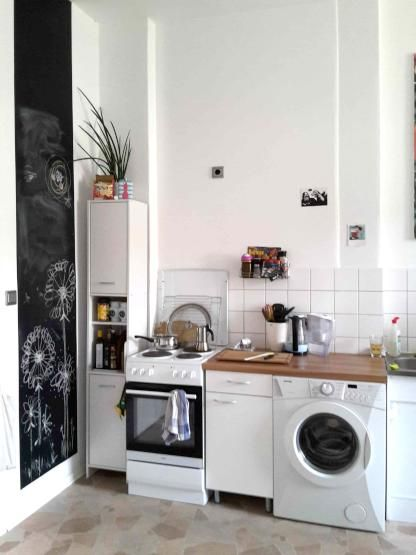 Schön eingerichtete, helle Küche mit Tafelwand für Notizen mit