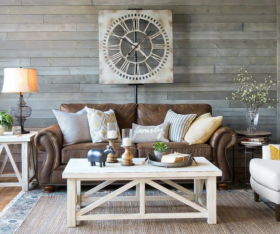 Farmhouse Living Room With Brown Leather Sofa And Distressed White Tables