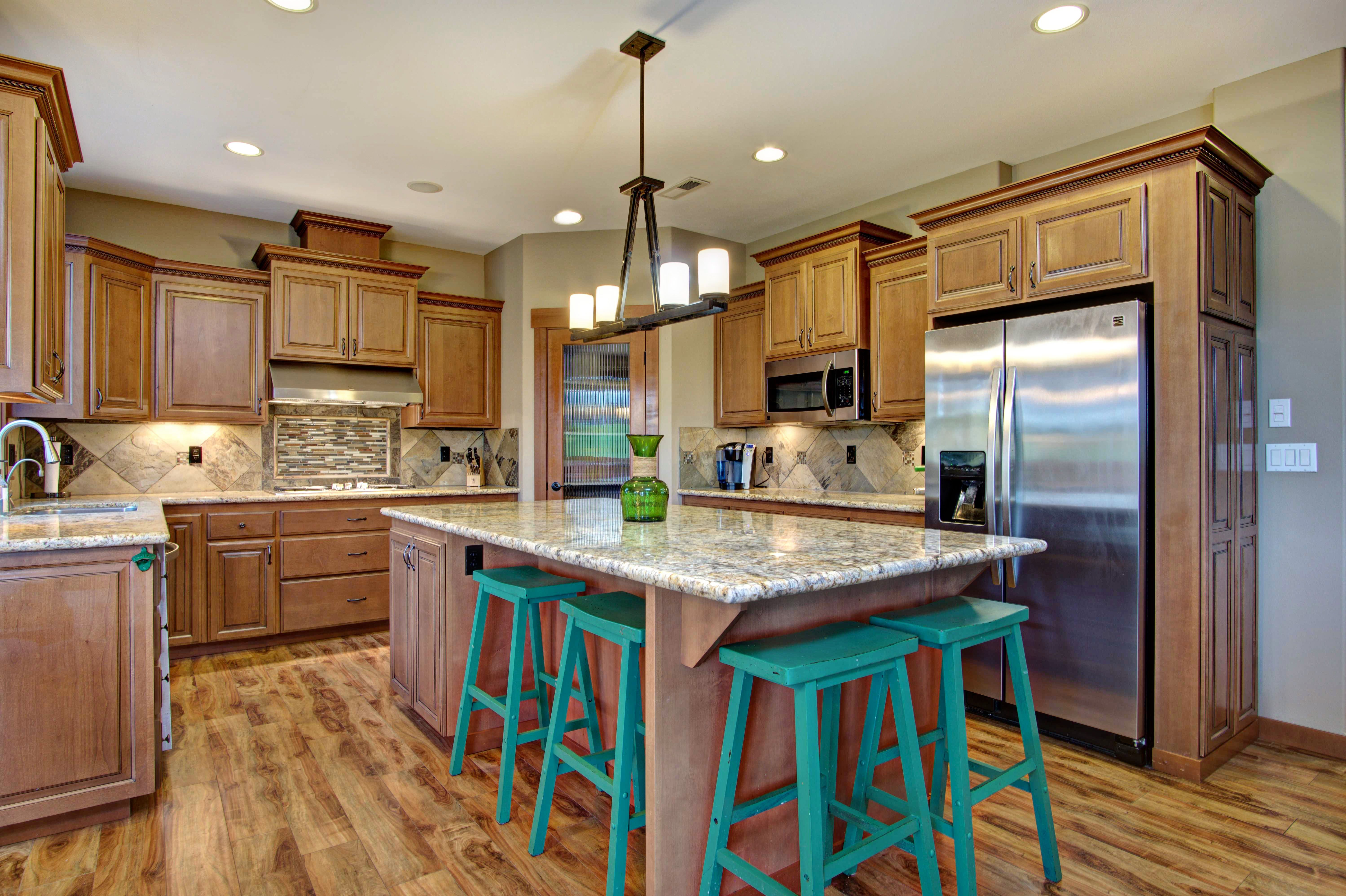 Staggered Cabinet Uppers Give This Kitchen Dimension And Style Large Island With Seating Slab Granite Staggered Cabinets Island With Seating Grey Backsplash